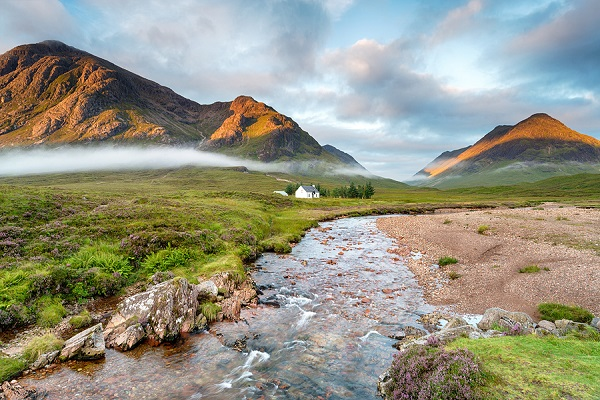 The rising sun lighting the mountain peaks at Glencoe in the Highlands of Scotland